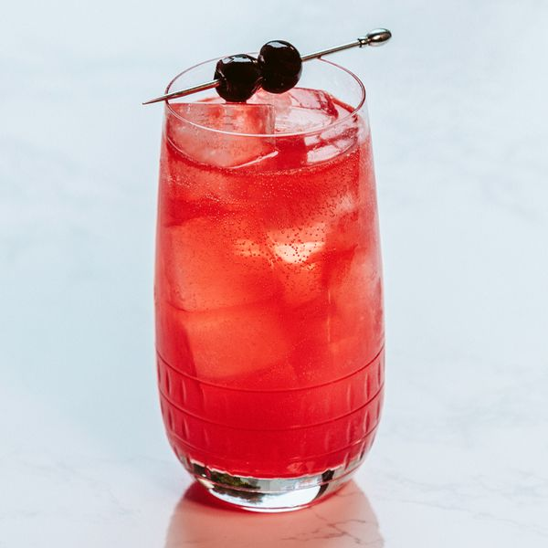 red-colored Don't Call me Shirley in a Collins glass with two skewered cherries balanced on the rim, served on a white surface