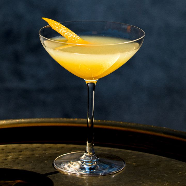 orange-colored Tequila Corpse Reviver in a coupe glass, garnished with an orange peel and served on a round tray