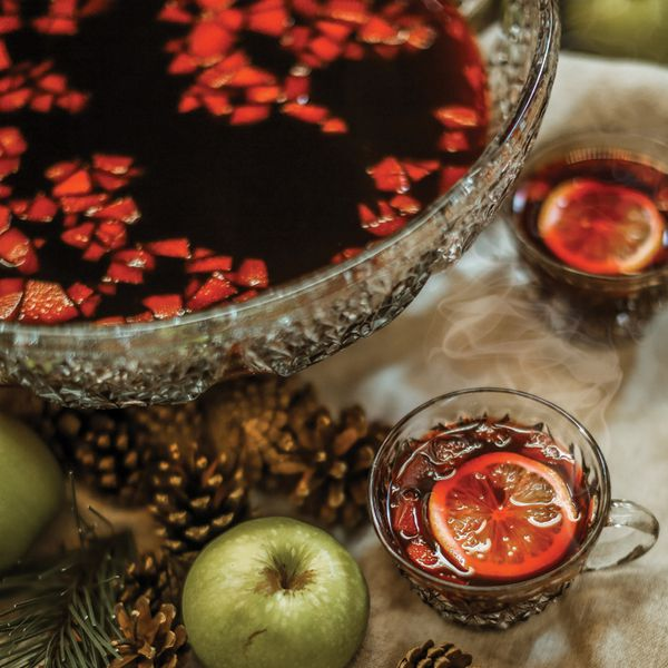 A large glass bowl filled with dark red punch rests on a white tablecloth, surrounded by gold pinecones, green apples and glass mugs of punch.