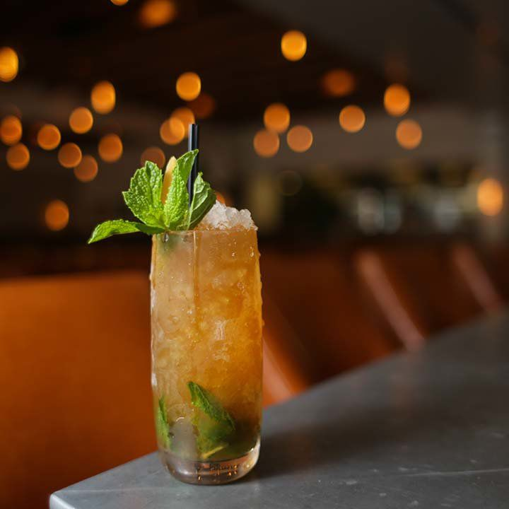 In the foreground, a tall collins glass is beaded with condensation and filled with crushed ice, muddled mint, and a dark brown drink. A bunch of mint and a thin black straw garnishes the drink. The background is an out-of-focus restaurant.