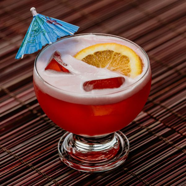 Ruby Relaxer cocktail with orange wheel and umbrella garnish