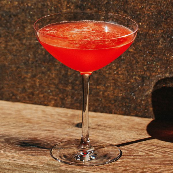 A bright red shaken cocktail in a coupe glass against a brown sparkly background