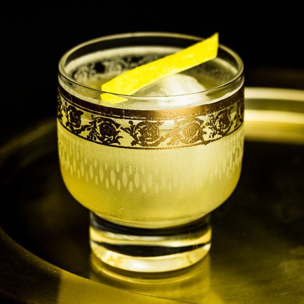 gold rush cocktail with lemon peel, served in an ornate glass on a circular tray