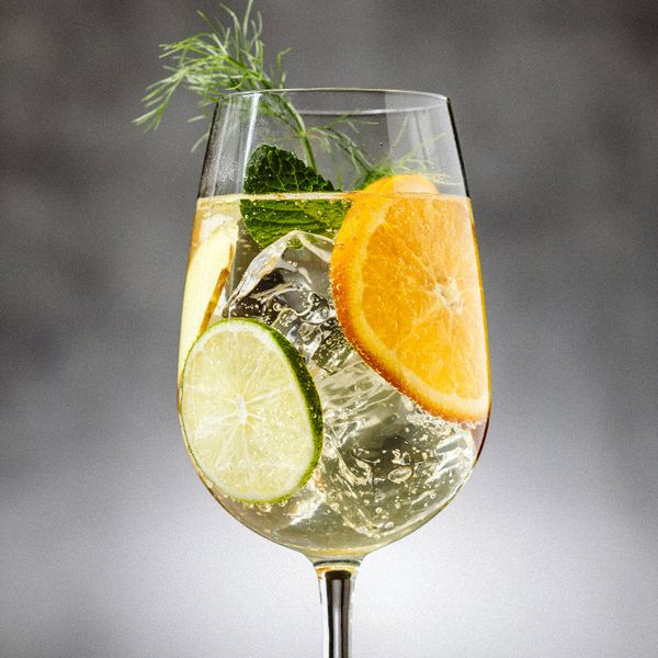 A wine glass holds a bubbly cocktail garnished with lime and orange wheels, mint leaves, and a fennel frond.