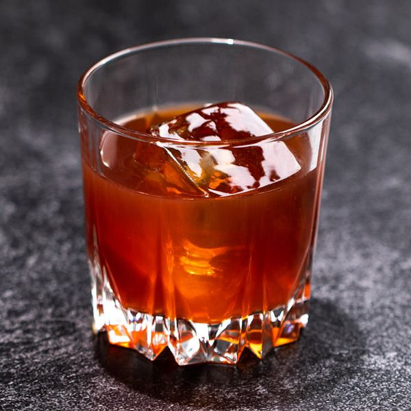 A faceted rocks glass rests on a dark gray surface. The glass holds a single large ice cube immersed in a red-orange drink.