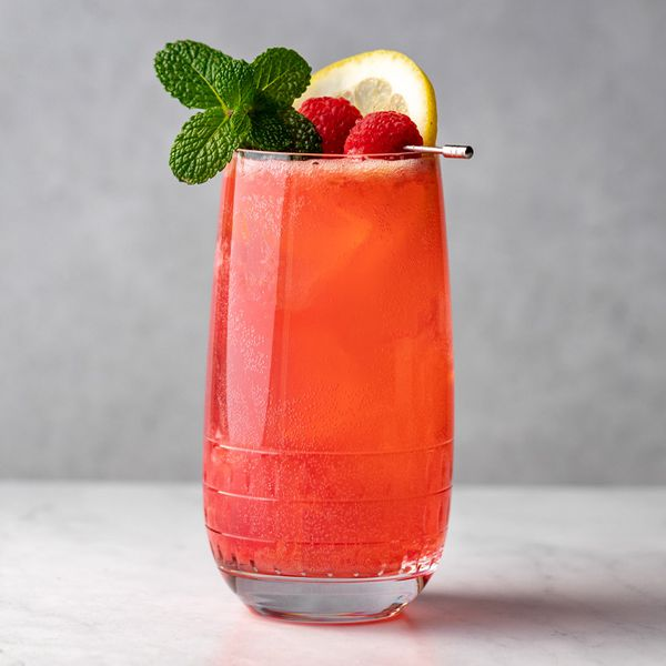 Raspberry Collins cocktail garnished with mint, lemon and raspberries