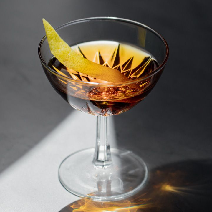 A faceted cocktail coupe sits on a marble surface. A beam of light illuminates a golden beverage within, and a thin slice of lemon peel. The rest of the photo is in shadow.