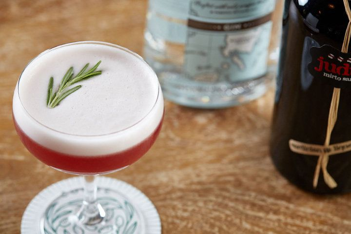 A frothy deep pink cocktail in a coupe garnished with a sprig of rosemary