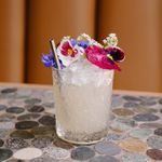 Rebirth cocktail in a textured rocks glass, served over crushed ice and garnished with purple, pink and white flowers and a metal straw