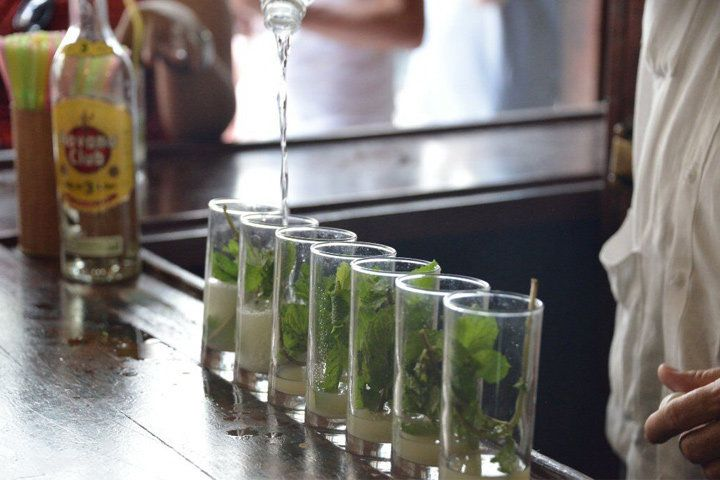Seven glasses with sugar and mint are lined up on a sunny bar. A man, mostly off camera, pours a long stream of soda water into one of them.