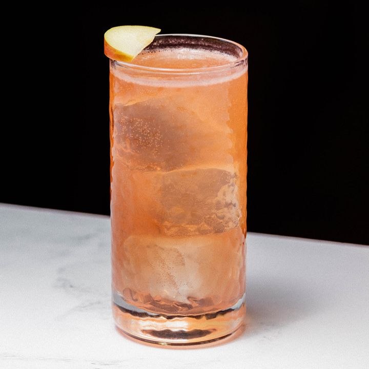 Set on a white marble surface against a stark black background, a thick highball glass is filled with a bubbly, orange drink and a few large ice cubes. A slice of apple rests on the rim of the glass.