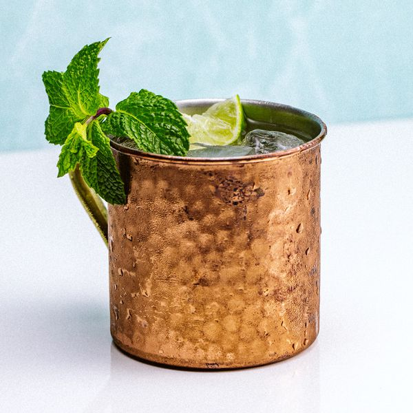 A hammered-copper Moscow Mule mug sits on a white surface. A large sprig of mint drapes over the mouth of the glass, with a lime wedge behind it. The background is minimal, and pale blue.