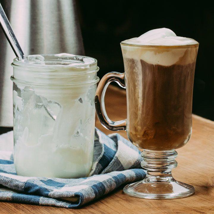 Irish Coffee Cocktail in glass mug next to a jar of cream