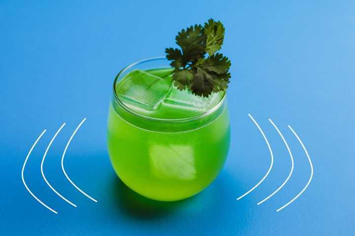 A jade colored cocktail with a few large ice cubes fills a curved rocks glass, topped with a sprig of cilantro. Its background is pure blue with a few emphasis lines