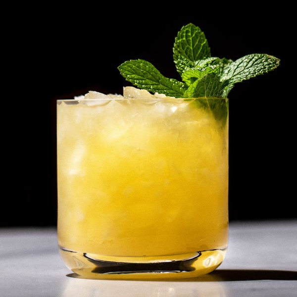 bright-yellow Bulldog Smash cocktail in a rocks glass, garnished with a sprig of fresh mint leaves