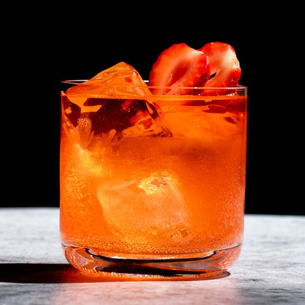 red-colored El Chapo cocktail in a rocks glass, garnished with two skewered strawberries slices
