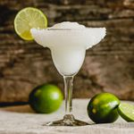 frozen margarita cocktail on cloth surface next to limes