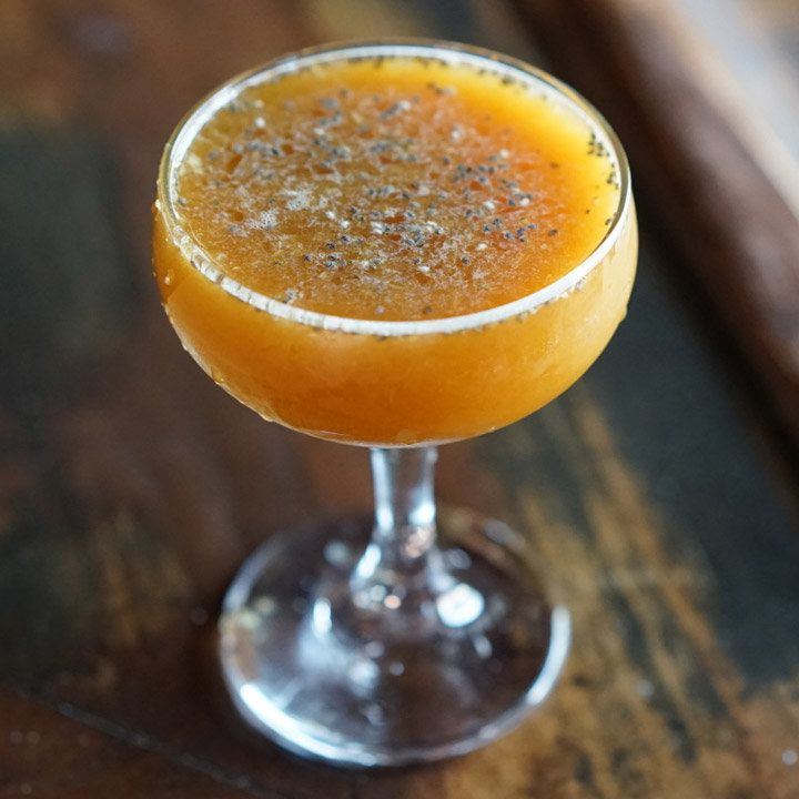 orange-colored valley of the dark lords cocktail with chia seeds on top