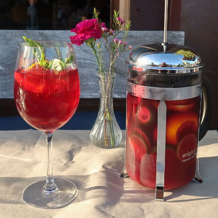 French Press Sangria on a table with wine glass and flowers