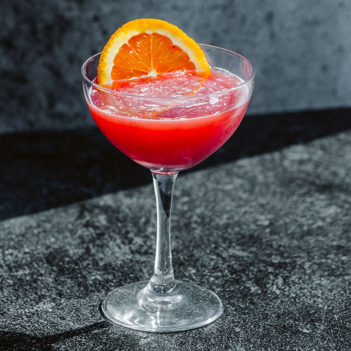 red-colored Tart 'n' Sand cocktail in a coupe with an orange wheel, set in a sunbeam on a dark granite counter