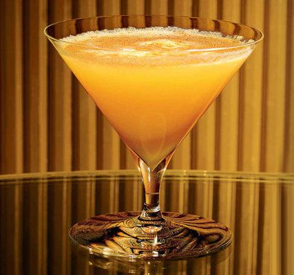 A warm golden-hued Margarita in a short-stemmed Martini glass against a gold background
