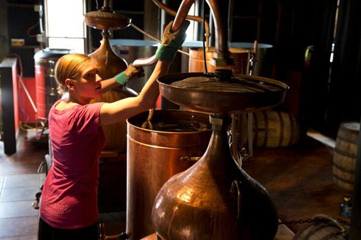 A distillery worker tending to copper pot still at the Montanya rum facility