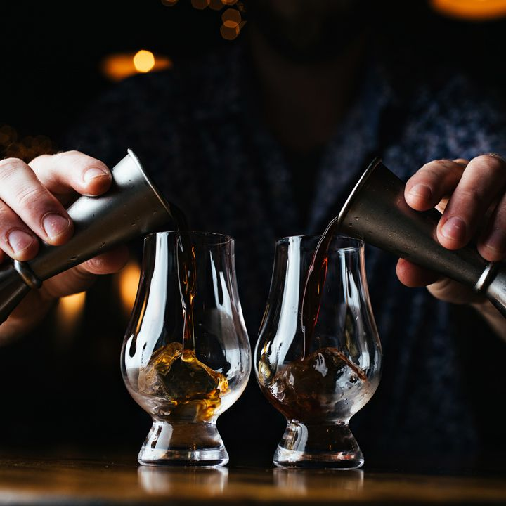 A bartender pouring kosher spirits from two jiggers into two tasting glasses