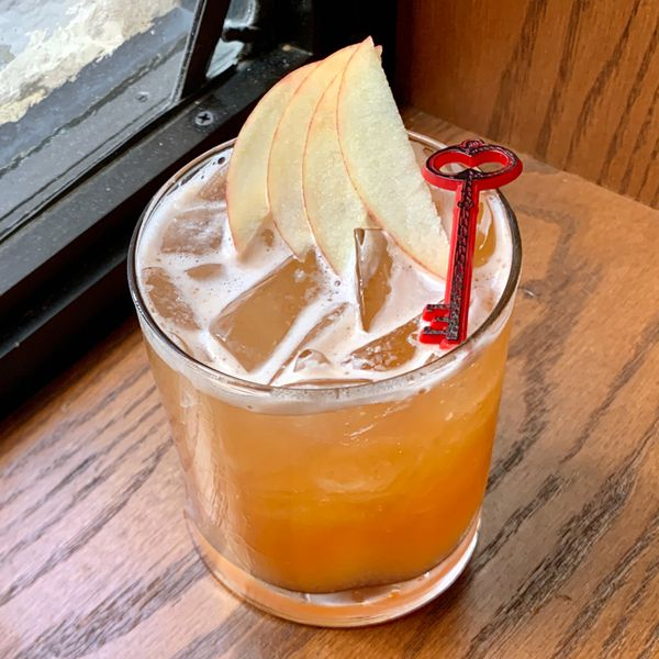 A short rocks glass sits in the corner of a wooden windowsill, a window just out of frame behind it. The glass is filled with ice and a red-orange drink, and is garnished with four thin slices of apple and a plastic red and black key.