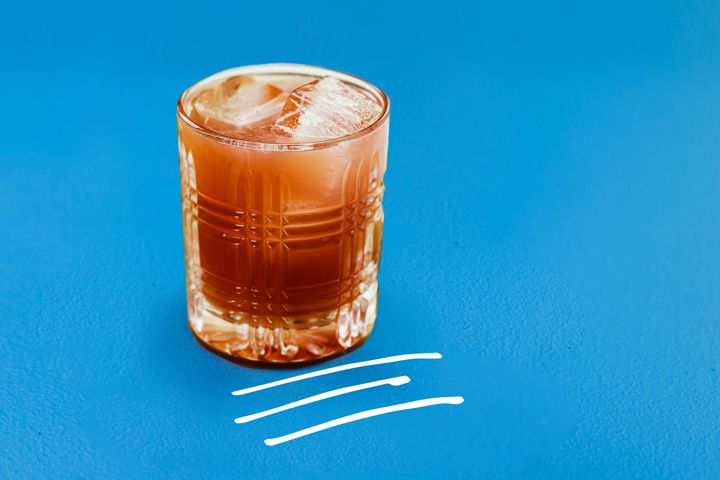 Photo illustration of red Port New York Sour in rocks glass on blue background with white hand-drawn lines