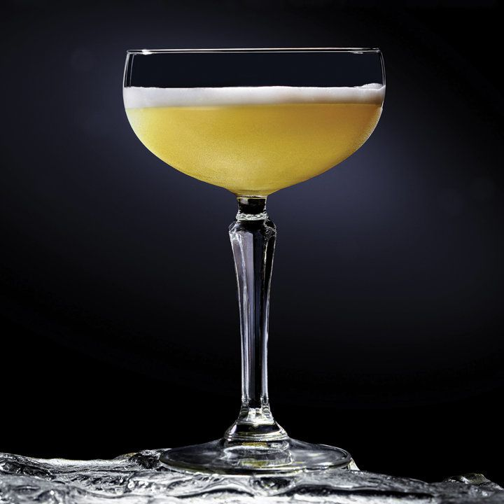 A large-stemmed cocktail coupe stands on an icy surface with a black background behind. The drink within is golden yellow, topped with white foam.