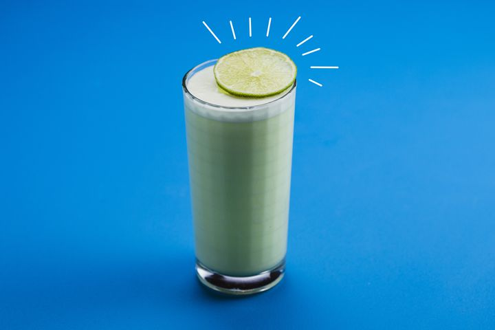 A tall, square-faceted collins glass is filled with an opaque, pastel green beverage, all on a solid blue backdrop. A wheel of lime rests atop the glass, emphasized with straight white lines