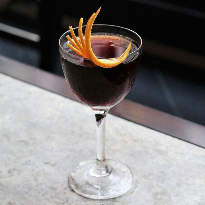 dark brown Spanish Armada cocktail with curled, fanned-out orange peel garnish in Nick & Nora glass