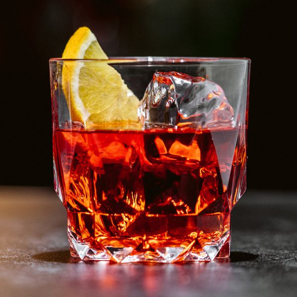 A beveled rocks glass with clear ice, a ruby-red Negroni, and an orange half-slice