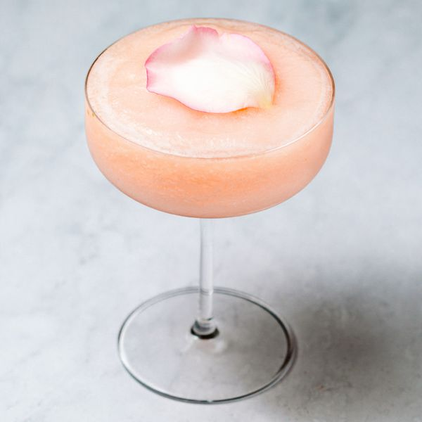 Icy, peach-colored Guava Rose cocktail in a coupe glass, garnished with a pink rose petal
