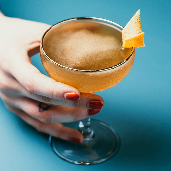 A hand with red fingernails holding a shaken drink in a coupe glass garnished with an orange twist