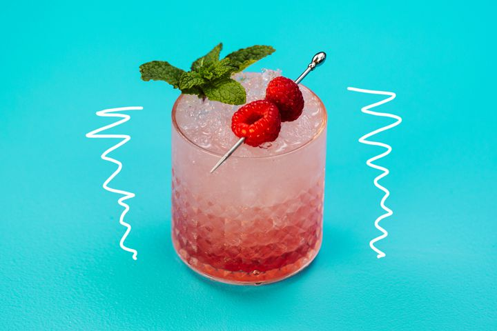 A short, detailed rocks glass holds a bright red drink over crushed ice. The drink is garnished with a sprig of fresh mint and two raspberries pierced on a silver pick. The glass is on a light blue background with a white squiggly line on either side of it.