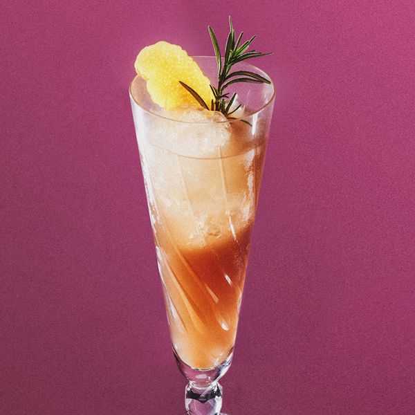 A tall, tapered flute glass holds a reddish sparkling drink, a few cubes of ice, a lemon peel and a sprig of rosemary. The background of the image is solid pink.