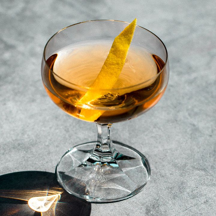 An elegant coupe with a faceted stem rests on smooth gray concrete. The glass holds a light amber drink and a thin slice of lemon.