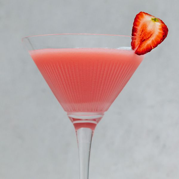 A faceted cocktail glass holds a vivid pink drink, and is garnished by a bright red strawberry half. The background is mottled gray.