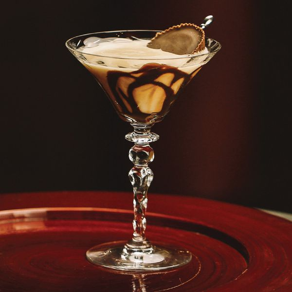peanut butter cup cocktail in stemmed glass on a round, red tray