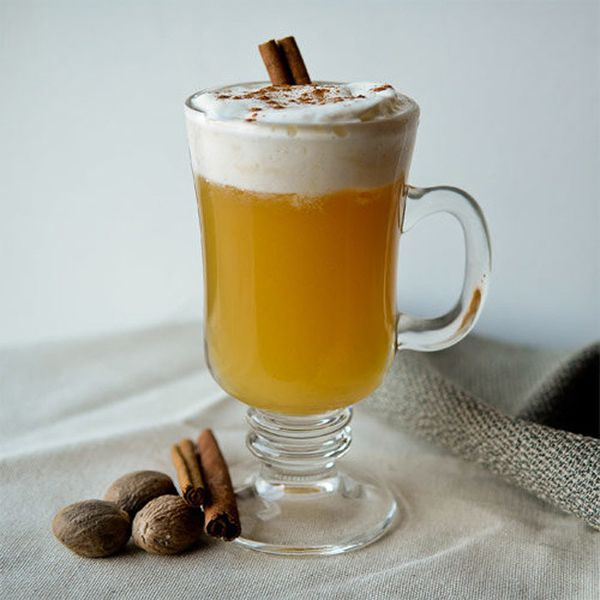 Heated Affair cocktail with white frothy head in an Irish coffee mug, garnished with cinnamon stick and fresh nutmeg