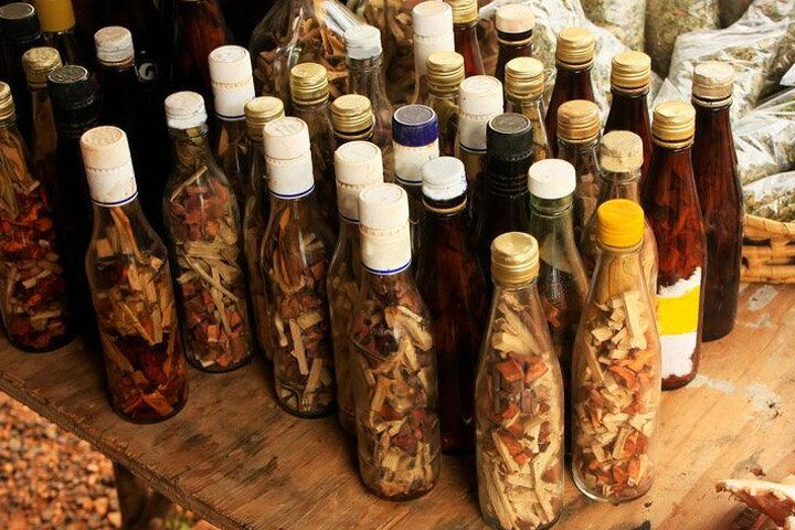 Various bottles filled with Mamajuana herbs, spices, and barks, some filled with liquid and others not