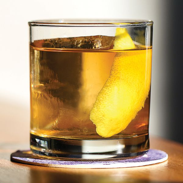 A rocks glass with a stirred brown cocktail on a large ice cube garnished with lemon zest