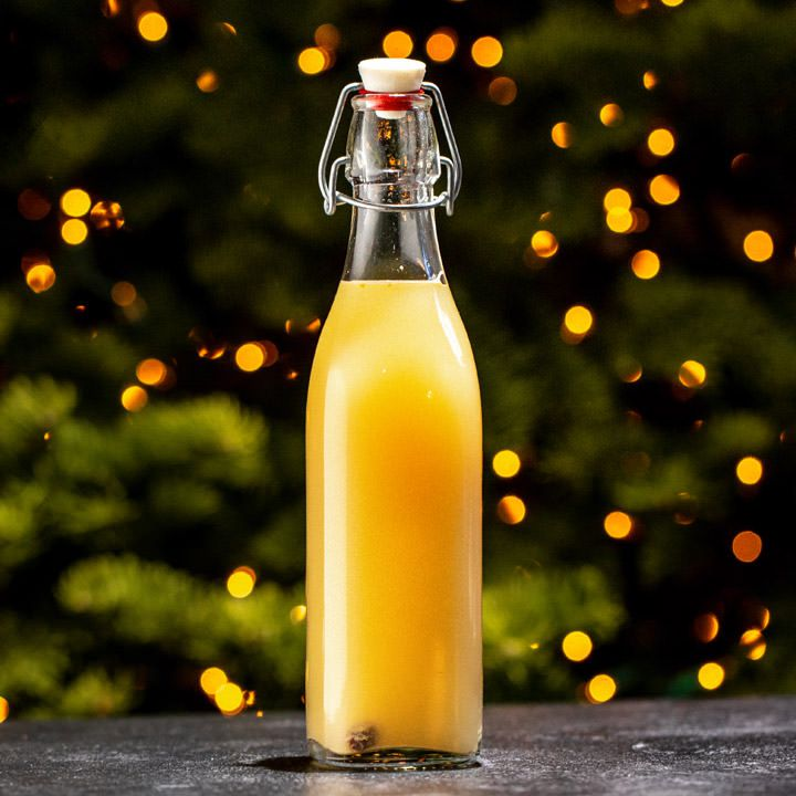 A golden, opaque beer fills a 250-milliliter stoppered bottle resting on a black marbled surface. The background is hazy and out of focus, with light coming through spruce trees.