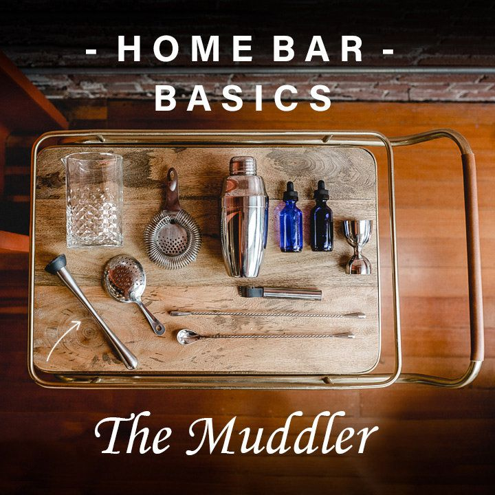 Aerial view of a wooden bar cart with various supplies and tools laid out, including a mixing glass, strainers, bar spoon, jigger and muddler