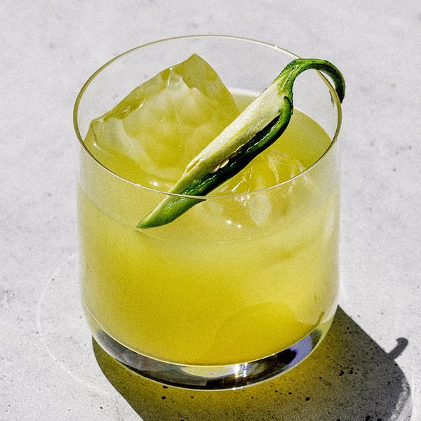 A rocks glass rests on a concrete surface. The glass holds a yellow-green beverage, a few ice cubes and a long sliver of jalapeno.