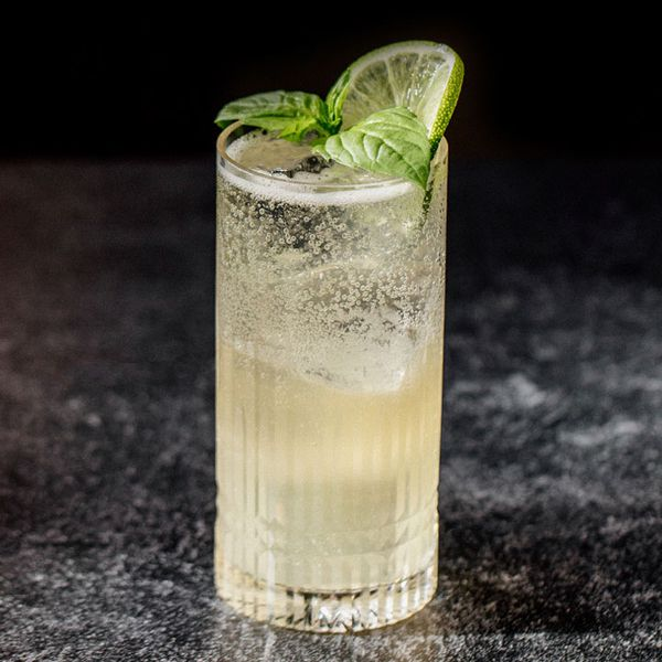A faceted highball glass rests on a black marble surface. It's filled with a pale soda and ice, and topped with basil leaves and a wheel of lime.